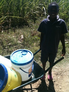 A boy bringing home water from a well for the day.
